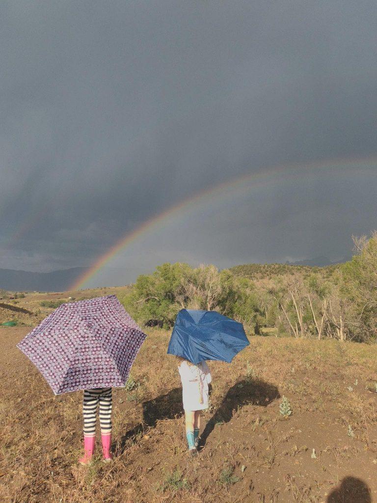 Two children with umbrellas under a rainbow