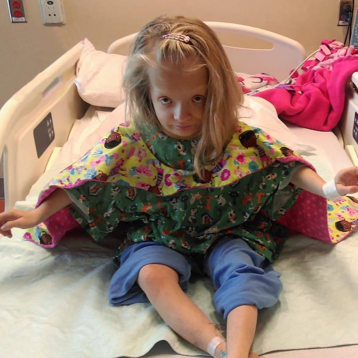 Girl in hospital bed with cape