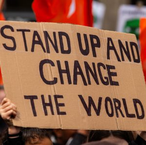 "Cardboard sign that reads ""Stand up and change the world"""