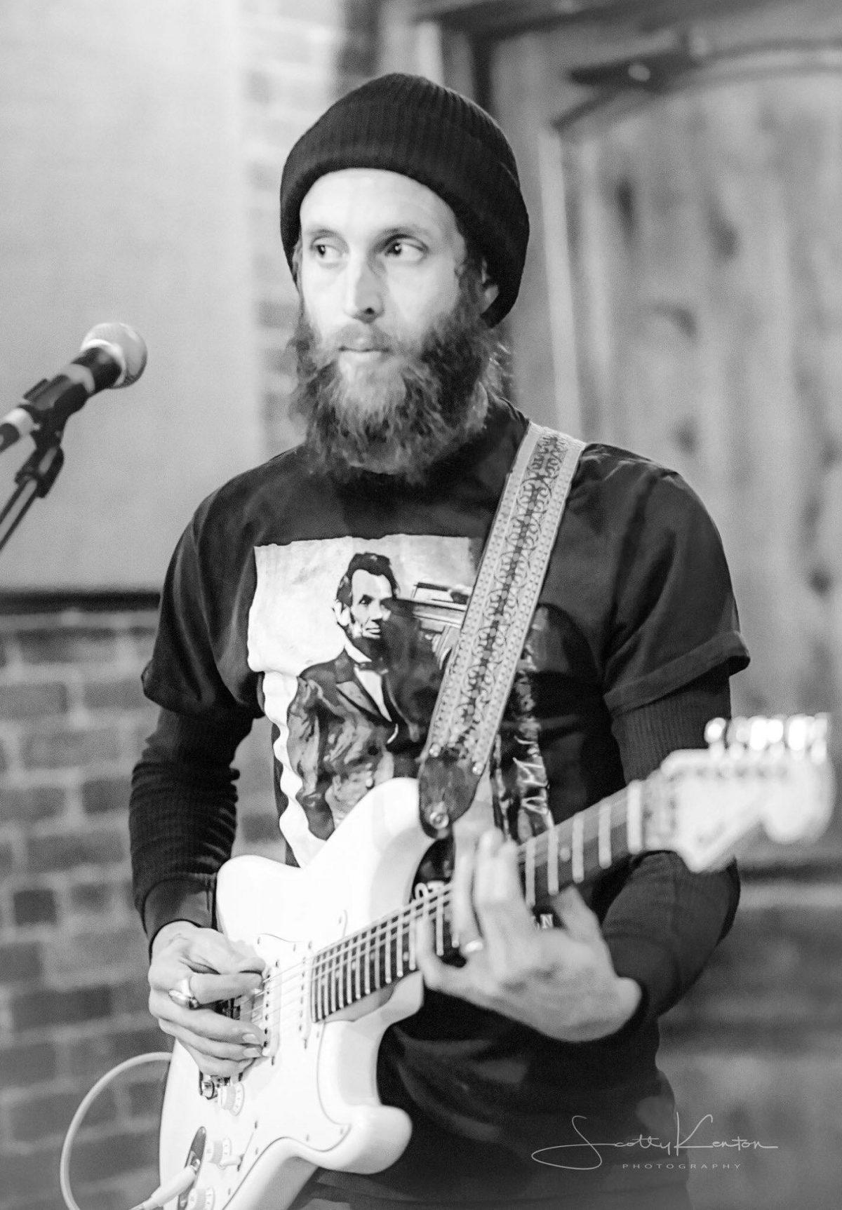 Man with a beard playing guitar